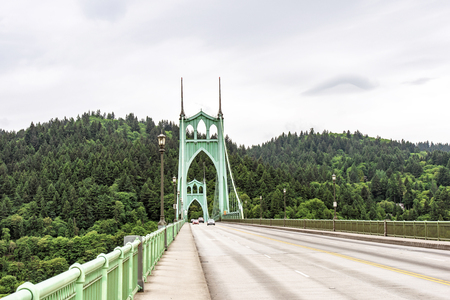 High powerful arch support of a gothic style long transportation St Johns Bridge with windows at the top and stretch marks that support the bridge across Willamette River in Portland industrial area