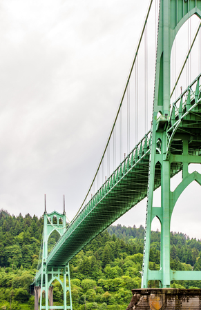 High arched rope support of a gothic style long transportation St Johns Bridge with windows at the top and stretch marks that support the bridge across Willamette River in Portland industrial area