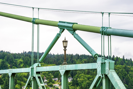 Famous gothic arched rope support of a long truss transportation St Johns Bridge with windows at the top and stretch marks that support the bridge across Willamette River in Portland industrial area