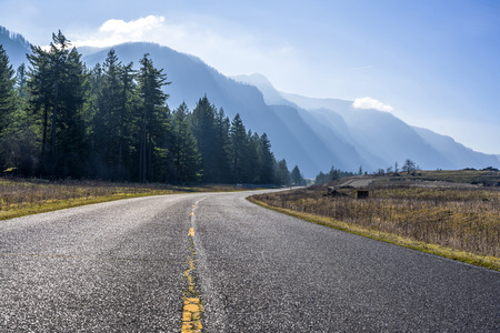 Road with separation marking rests on high mountains on the banks of the Columbia River, lit by bright slanting sunlight and trees on the banks in the Columbia River Gorge National Recreation Reserve 写真素材