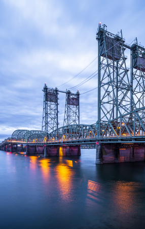 Drawbridge arched truss Columbia Interstate bridge over the Columbia River with evening lights with lift towers for lifting the bridge section for the passage of vessels connect Oregon and Washington 스톡 콘텐츠