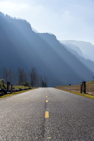 Road with separation marking rests on high mountains on the banks of the Columbia River, lit by bright slanting sunlight and trees on the banks in the Columbia River Gorge National Recreation Reserve 免版税图像