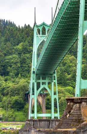 Famous gothic arched rope support of a long truss transportation St Johns Bridge with concrete columns and stretch marks that support the bridge across Willamette River in Portland industrial area Banco de Imagens