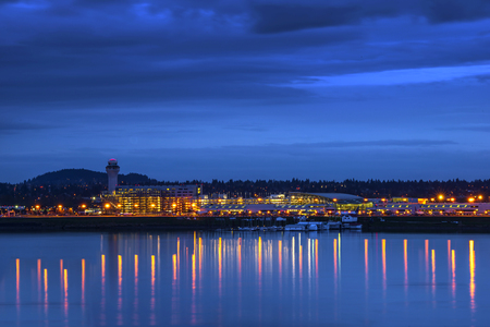 Evening view of the PDX Portland airport with traffic control tower, lights and reflection in the river, where boats are parked. In the lights parking of cars, aircraft, maintenance cars and trucks. 스톡 콘텐츠