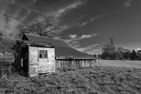 An old dilapidated non-residential barn without a shed with an extension without doors and broken windows stands in the middle of the field as a reminder of transience of time and rapid development of civilization