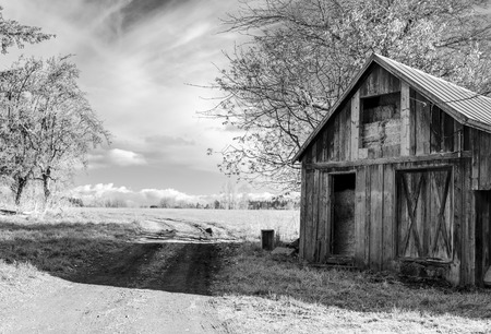 Old abandoned barn with pressed hay and a road across meadow without doors and windows stands in the middle of the field as a reminder of transience of time and rapid development of civilization