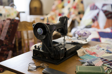 An old foot-operated sewing machine in a room used as a sewing workshop with patches of various fabrics and already stitched products hanging around is a real creative place of the past Standard-Bild - 117553489