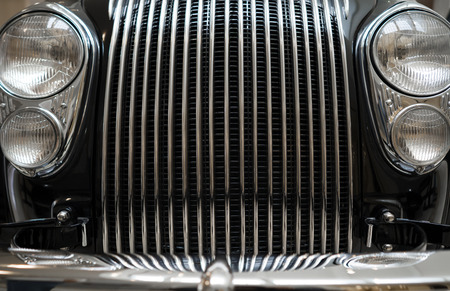 Fragment of a vintage black car with a surprisingly elegant grille design, made of chrome strips and a headlight in a chrome-plated case, blending in with the car's geometric shapes Фото со стока