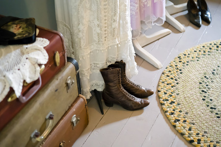 Vintage dressing room with old clothes, handmade lace dresses, leather model shoes, hand-woven carpet of cloth strips, suitcases with snaps - an illustration of a frozen past century