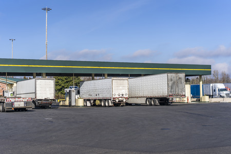 Big rigs commercial cargo haulers Semi Trucks with different semi trailers of various brands and models fill the tanks at the filling station to continue the delivery routes of industrial goods Stockfoto