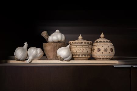Still life with wooden jars for spices, painted with Ukrainian folk ornament, and wooden mortar with pestle for grinding spices, and garlic heads, dried for long-term use Standard-Bild