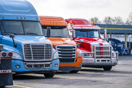 Different bonnet makes and models of professional big rigs semi trucks with commercial cargo on semi trailers standing in row on the industrial truck stop parking lot waiting for unloading