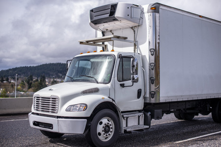 The middle-duty white day cab compact semi truck for local shipping and delivery services with refrigerated box trailer running on the wide highway to deliver loaded chilled fresh produce Stock Photo