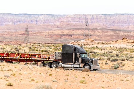 Black big rig American semi truck transports radioactive substances in containers mounted on flat bed semi trailer driving through the desert in Arizona, what is dangerous and responsible work