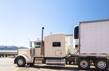 White big rig beautiful classic American powerful semi truck with chrome exhaust pipes with attached refrigerated semi trailer with refrigerator unit on it standing on truck stop parking lot in Utah
