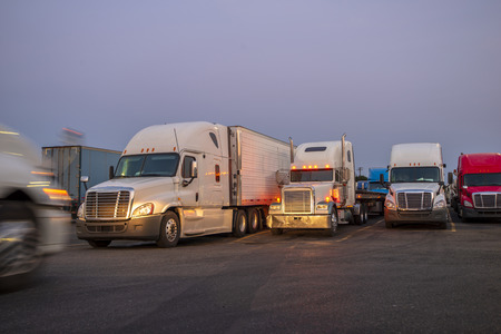 Different makes and models professional commercial bonnet big rigs semi trucks with semi trailers standing in row on the twilight truck stop and illuminated by the headlight of passing semi truck