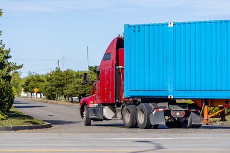 Powerful long haul red big rig semi truck with high cab for truck driver comfort and reduce trailer aerodynamics transporting blue long container turning on the local road with green trees alley