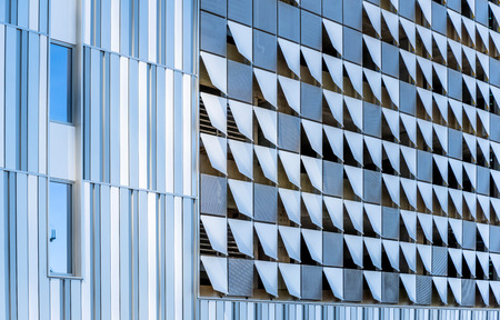 Elements of modern city architecture decorative abstract metal suspended facing of the external walls of a sunlit multistory building, made in the form of various curved squares in residential area Stok Fotoğraf