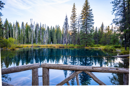 The mysterious landscape of a very deep cold Little Crater Lake surrounded by wild forest is a popular place for tourists and people who prefer an active lifestyle to spend their time in the wild