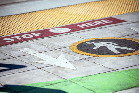 Color road markings for pedestrians at the intersection indicating the direction of movement of pedestrians, indicated by a round sign, and a safe stop line to wait for a traffic light signal 스톡 콘텐츠 - 121430988