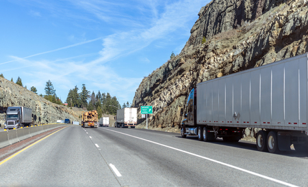 Big rigs American freight semi trucks with loaded semi trailers running on mountain pass in California are moving along all lanes of the highway including along the side of the road in the brake lane Stockfoto