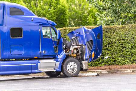 Broken American industrial grade freight transportation blue big rig semi truck tractor with an open hood stands on the truck stop parking lot waiting for mobile repair on site