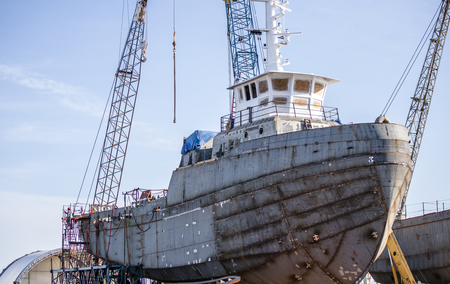 Shipyard on which build a ship or yacht with hold, navigation wheelhouse and cabins welded from sheets of metal mounted on special supports around which construction work continues to be carried out