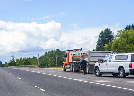 A police officer in uniform stopped a big rig semi truck for check a truck driver and inspection of a tip truck and approaches to the truck on the side of the road, visually inspecting a tip truck Banco de Imagens
