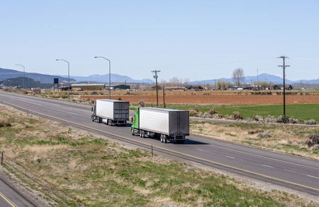 Two big rig industrial grade American freight transportation semi trucks transporting perishable commercial cargo at reefer semi trailers running on the divided highway on flat plateau in Utah Stock Photo