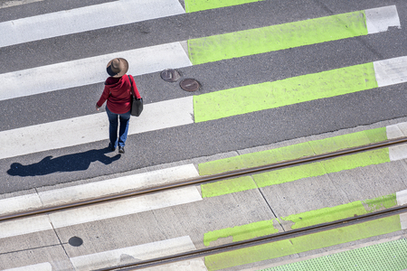Elegant slender woman in a hat, red cardigan and jeans crosses the road on a zebra pedestrian crossing observing the rules of the road to protect your life from collisions with a car in sunny day Stock Photo