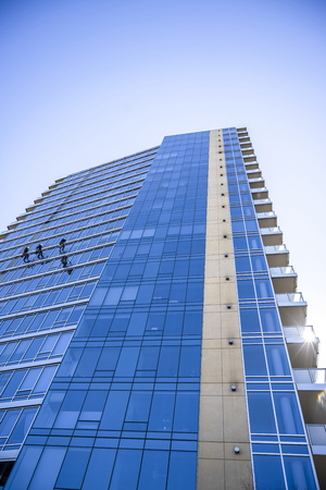 Window washers in special equipment with the necessary tools and detergents, like climbers, descend on the ropes from the roof of a skyscraper, each washes out a certain area of a building windows Stok Fotoğraf