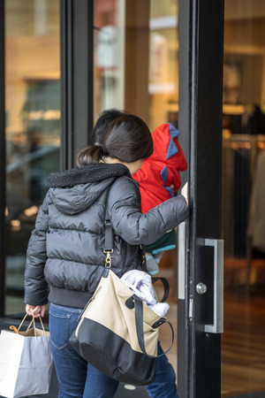 Two gentle girls with already made purchases and stock it in the bags, love to go shopping and opening door to go to the next clothing store, hoping to buy goods at a discount on sale
