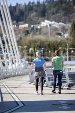 Two women talk animatedly while walking along Tilikum Crossing bridge combining pleasant conversations with each other with useful exercise in walking to strengthen muscles and improve metabolism