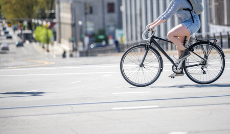 Woman rides a bike on city street. The use of a bicycle as the main transport for many enthusiasts has grown from a hobby into a vital necessity for maintaining health and environmental concerns