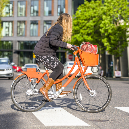 Gorgeous woman cyclist cross the crossroad on an orange rented social bicycle with basket preferring an active way of relaxation helping to keep herself in good shape in a good fit and enjoy life