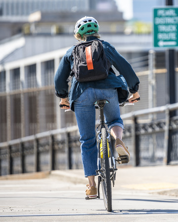 Woman rides a bike on a bike path. The use of a bicycle as the main transport for many enthusiasts has grown from a hobby into a vital necessity for maintaining health and environmental concerns