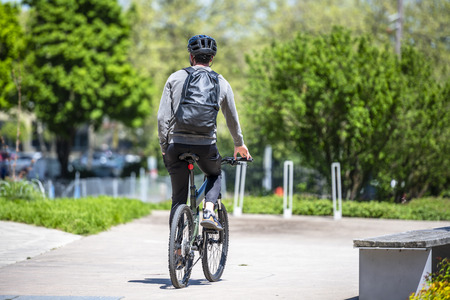 A man on a bicycle pedals a bicycle, preferring an active healthy lifestyle using cycling and alternative environmentally friendly mode of transport in order to preserve the environment of his city
