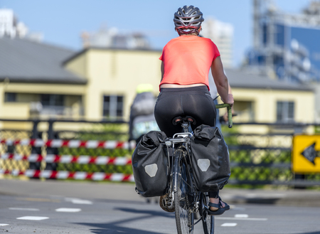 A gorgeous woman cyclist in sportswear and helmet crosses the crossroad on a bicycle, preferring an active way of relaxation, helping her to keep herself in good shape, in a good fit and enjoy life Stock Photo