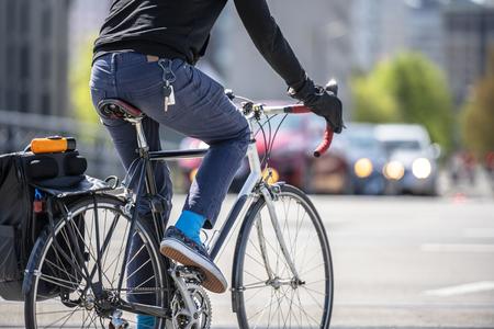 Ein Radfahrer tritt ein Fahrrad und fährt durch die Straßen der Stadt Portland, wobei er, wie die meisten Einwohner von Portland, einen aktiven, gesunden Lebensstil und ein alternatives umweltfreundliches Verkehrsmittel bevorzugt
