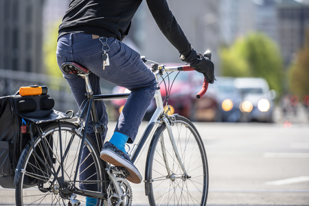 Man cyclist pedals a bicycle and rides along the Portland city streets, preferring, like most Portland residents, an active healthy lifestyle and an alternative eco friendly mode of transport