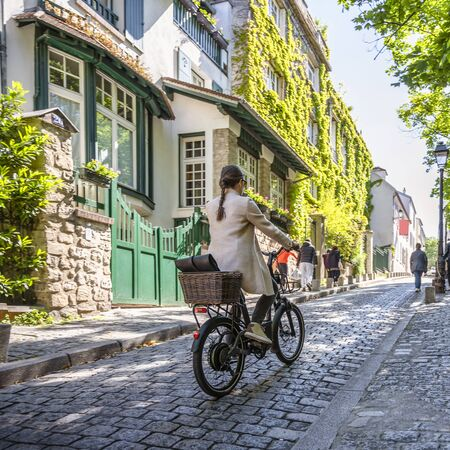 Riding a bike in Montmartre Paris is not only useful but also beautiful. Cycling combines the elegance of movements emphasizing the advantages of a female figure and effect of a slim elastic body Stock Photo