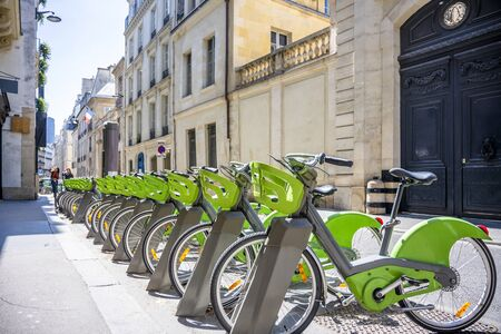 Street transportation green public rent bicycles with basket for traveling around the Paris city stand in row on rental network parking lot waiting for cyclists ready to make an exciting bike trip 免版税图像