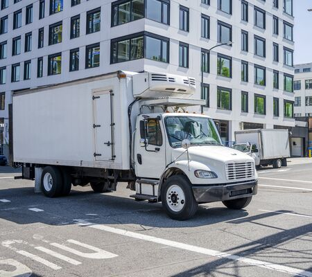 Small compact rig semi truck with refrigerator unit on box trailer transporting frozen and chilled foods on the street of urban city with multilevel buildings