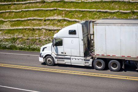 Camion semi-remorque blanc à grande plate-forme longue distance avec cabine haute pour le confort du conducteur de camion et réduire l'aérodynamisme de la remorque transportant des marchandises commerciales circulant sur la route avec de l'herbe verte sur la colline Banque d'images
