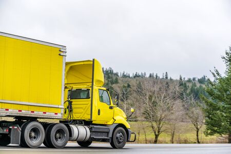Bright Yellow big rig day cab semi truck for local deliveries with aerodynamic spoiler on the roof transporting yellow dry van semi trailer on the road with trees on the side