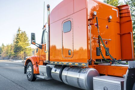 Bright orange classic iconic American big rig long haul professional comfortable powerful semi truck transporting commercial cargo in semi trailer driving on the wide divided multiline highway
