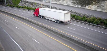 Rouge vif classique emblématique américain gros camion long-courrier professionnel confortable puissant semi-camion transportant des marchandises commerciales dans une semi-remorque conduisant sur l'autoroute multiligne large divisée