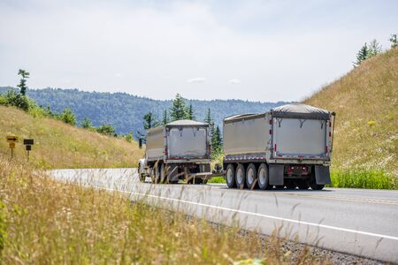 Big rig powerful industrial brown tipper semi tuck tractor with two dump trailers for heavy loads running on the winding road in green trees forest with hills in Columbia Gorge area Stock Photo