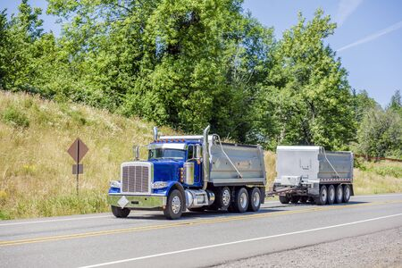 Blue Big rig powerful industrial brown tipper semi tuck tractor with two dump trailers for heavy loads running on the winding road in green trees forest with hills in Columbia Gorge area