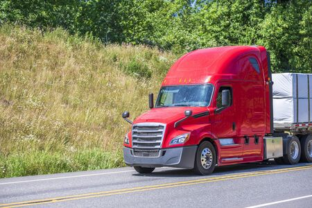 Big rig red classic long haul semi truck with flat bed semi trailer transporting tightened packed industrial lumber boards running on the turning winding road with hills and trees in sunny day